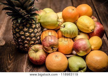 Tasty fruit background with orange kiwi grape apples and lemon on the wooden table