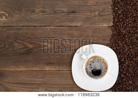 Coffee Beans And White Cup On Wood Table