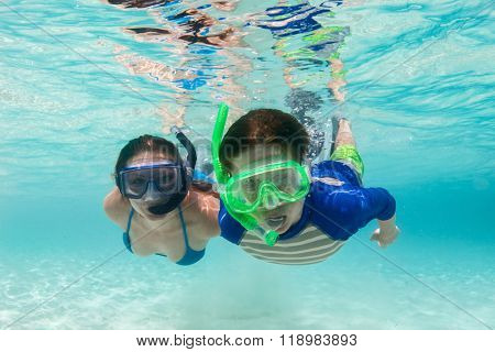 Underwater photo of mother and son family snorkeling in turquoise ocean water