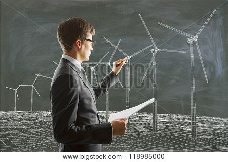 Businessman Paints Wind Generators On The Blackboard And Carries Paper