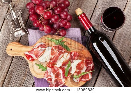 Prosciutto and mozzarella with red wine on wooden table. Top view