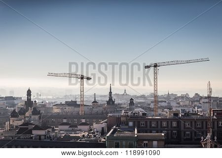 Two Big Hoisting Cranes Towering Above The Madrid City Rooftops