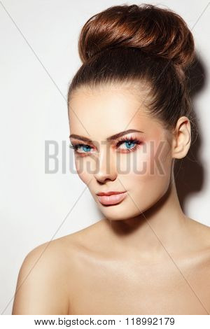 Young beautiful healthy woman with stylish make-up and hair bun