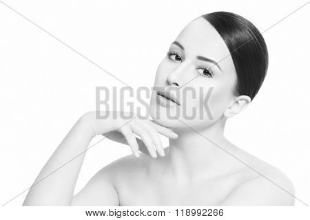 High key monochrome portrait of young beautiful healthy woman touching her face, over white background, copy space