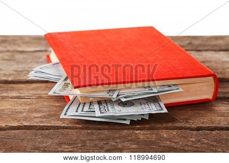 Red book with nested dollar banknotes on white background. Stash of money