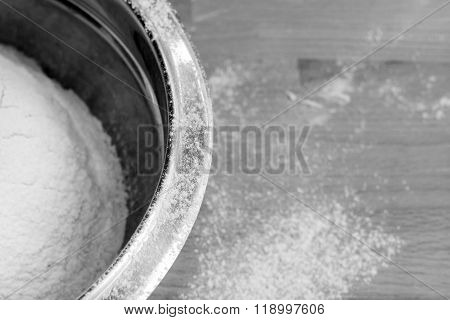 Flour in bowl on wooden table background. Black and white image