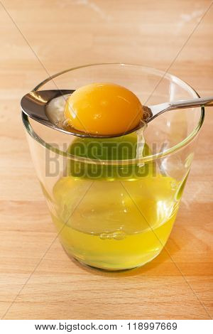 Raw egg yolk in spoon and glass with white