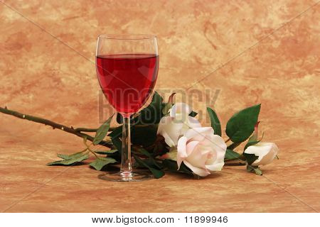 Glass of red wine and white roses