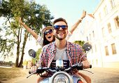 Portrait of happy young couple on scooter enjoying road trip poster