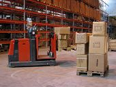 foto of lift truck  - A truck lifting a pallet of wares inside a warehouse - JPG