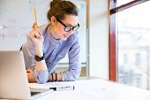 Happy young woman in glasses standing near the window in office and working with blueprint  poster