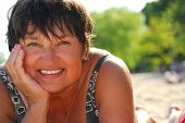 stock photo of middle-age  - portrait of a mature woman lying on a sandy beach - JPG