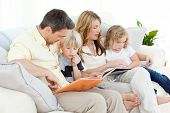 image of girl reading book  - Family reading a book on their sofa at home - JPG
