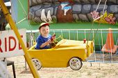 stock photo of carnival ride  - young boy riding yellow car at fairground sideshow - JPG