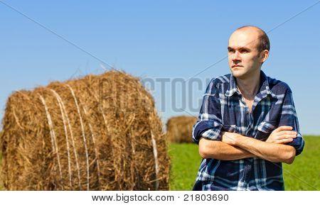 Farmer In Field Against Wheat Bales
