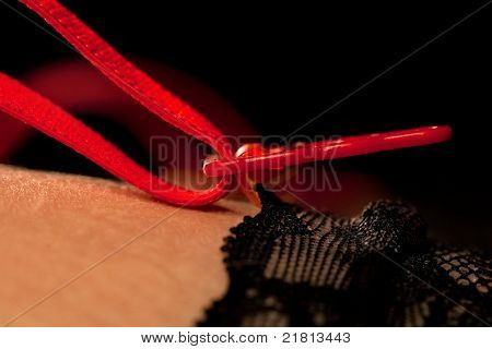 Beautiful woman's thigh in black stockings with red suspenders, close-up