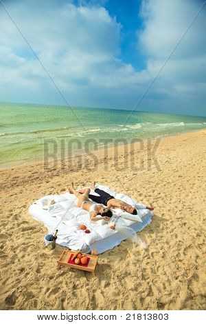 Beautiful young couple resting in bed in morning on the beach