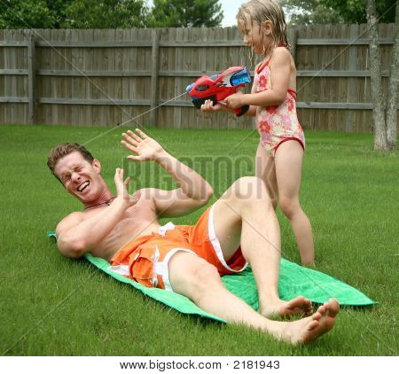 Backyard Fun As Girl Squirts Dad With Watergun
