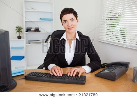 Smiling Secretary Typing On Her Keybord