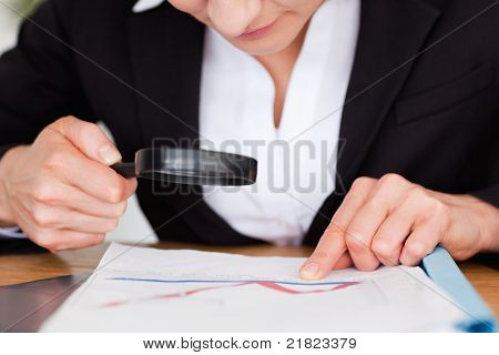 Feminine Hands Holding A Magnifying Glass Above A Chart