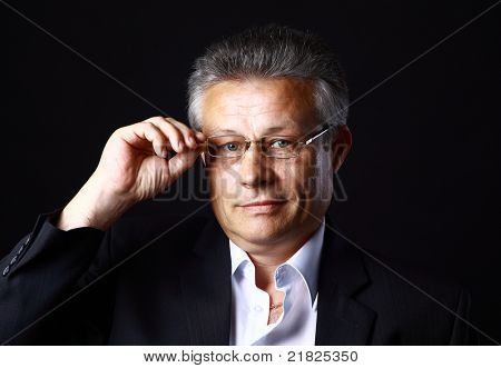 Portrait of successful business man standing on black background