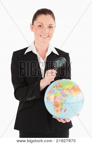 Charming Female In Suit Holding A Globe And Using A Magnifying Glass
