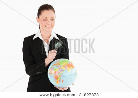 Cute Female In Suit Holding A Globe And Using A Magnifying Glass