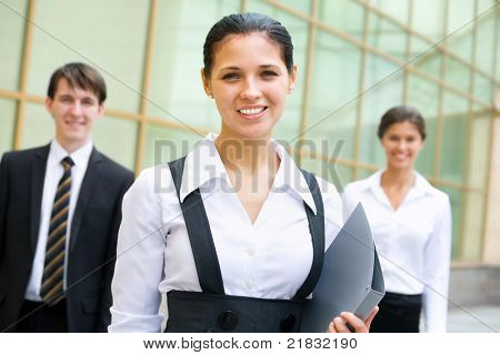 Portrait of a business woman with two of her co-workers on background  modern office building