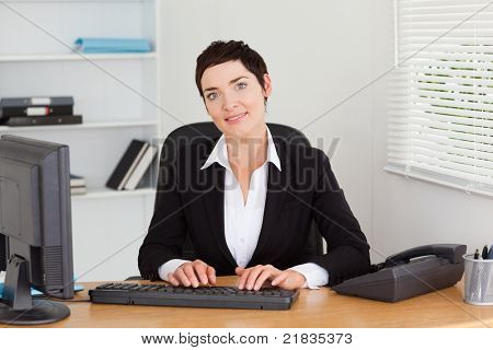 Young secretary typing on her keyboard in her office