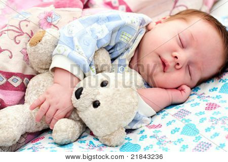 portrait of a sleeping baby with a toy
