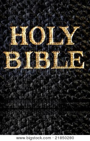 Holy Bible.  Gold letters on antique Bible, in close-up.