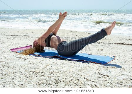 Woman Doing Yoga Exercise On Beach In Full Expression Of Fish Pose