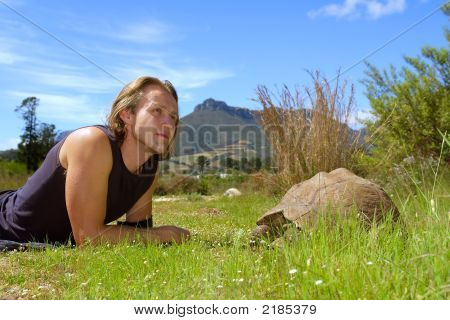 Man Looks At Skies Lying Next To Giant Turtle