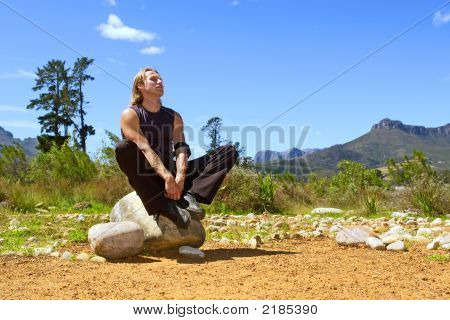 Young Attractive Man Is Meditating While Sitting On Rock