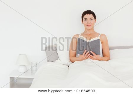 Brunette holding a book while looking at the camera