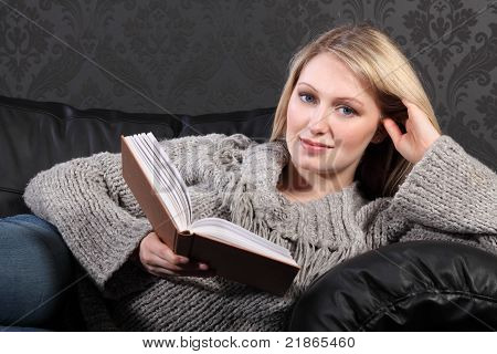 Smiling Blonde Woman Relaxing Reading Book At Home