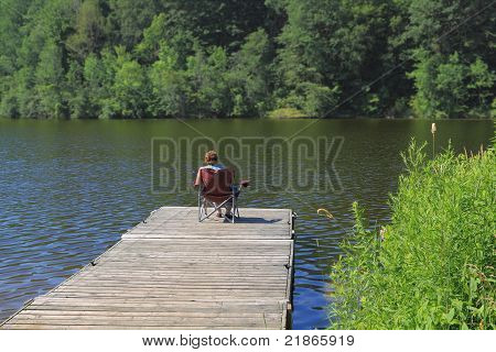 Elderly Woman Fishing From The Dock.