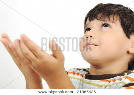 little muslim kid is praying on traditional way