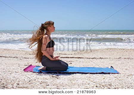 Woman Doing Yoga Exercise On Beach In Virasana Or Hero Pose