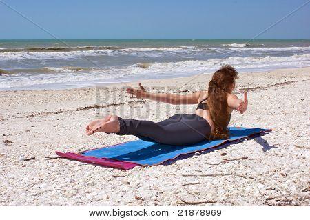 Woman Doing Yoga Exercise On Beach Shalabhasana Or Locust Pose