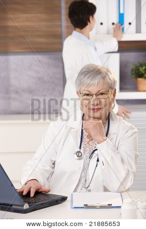 Senior doctor sitting at desk with laptop, smiling at camera, assistant looking at folder in background.?