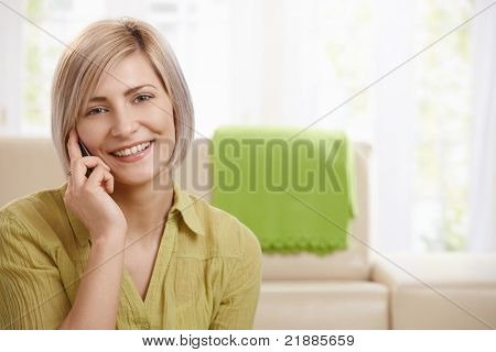 Portrait of attractive young woman speaking on mobile phone at home, smiling at camera.?