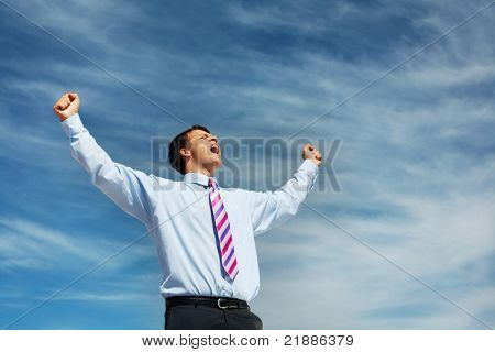 Photo of happy winner screaming from joy on background of blue summer sky