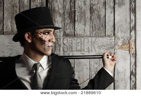 Fantastical stylized portrait of man in top hat and and cane in surrealistic makeup