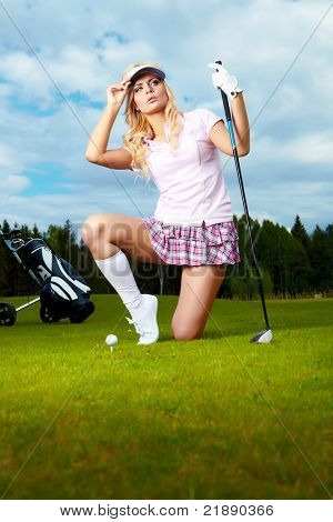 Woman placing a golf ball on the course