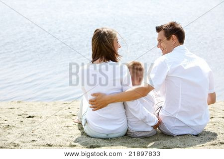 Backs of happy family sitting on sandy shore in front of blue water