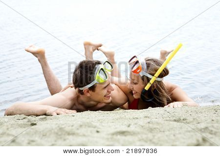 Portrait of cheerful couple in diving equipment lying on sandy shore