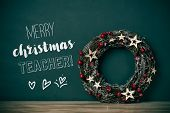 a nice christmas wreath with red fruits and golden stars, and the text merry christmas teacher in a  poster