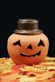 image of jack-o-laterns-jack-o-latern  - A pumpkin sits in a pile of fallen leaves - JPG