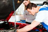 stock photo of car repair shop  - Woman talking to a car mechanic in his repair shop - JPG